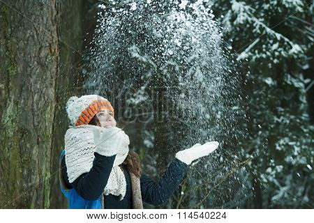 Cheerful girl tossing up fresh snow in winter outdoors