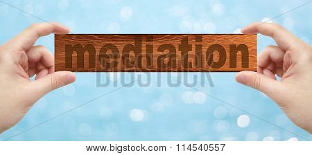 Hands Holding A Wood Engrave With Word Mediation