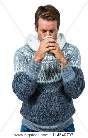 Man sipping coffee while standing against on white background
