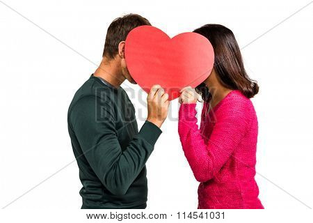 Couple covering faces with heart shape on white background