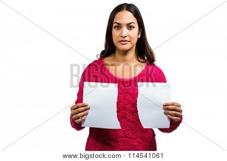 Portrait of woman holding torn documents while standing on white background