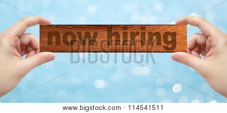 Hands Holding A Wood Engrave With Word Now Hiring