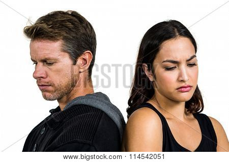 Upset couple standing back to back against white background