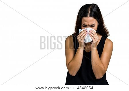 Unhappy woman blowing nose against white background