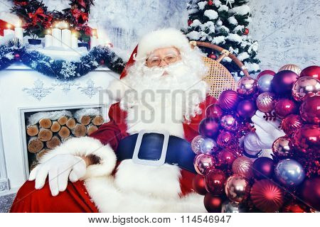 Happy Santa Claus sitting in a rocking chair with Christmas wreath in his arms. He is in the room by the fireplace and Christmas tree, beautifully decorated for Christmas.