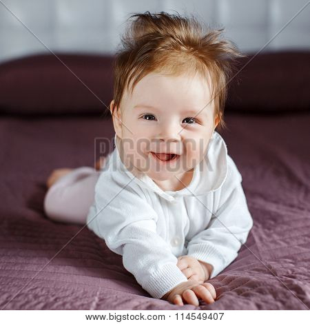 Portrait of a happy baby crawling on the bed