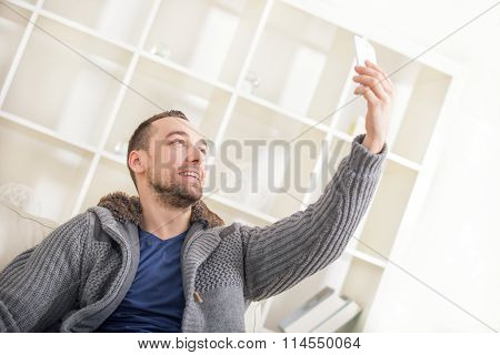 Young attractive 30s man taking selfie picture or self video with mobile phone at home