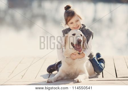 Little girl with his beloved dog at the lake