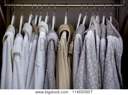 Bathrobes with hangers in wardrobe