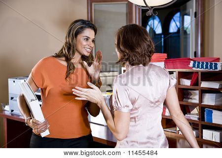Female Office Workers Chatting In Copy Room