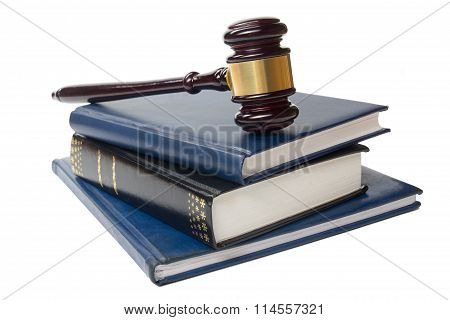 Law book with a wooden judges gavel on table in courtroom