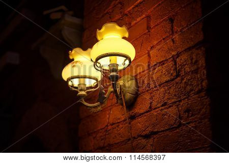 The lights at brown brick wall, around all is dark.