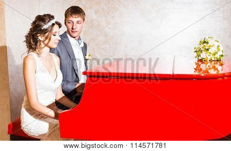 charming wedding couple playing on a red piano in the room