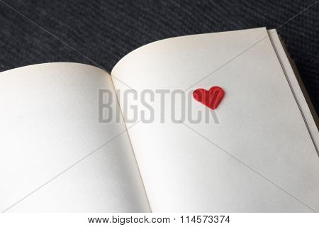 Red decorative heart on a book page. A novel about love