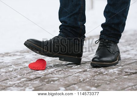 Symbol of end of love. Man treads decorative red heart