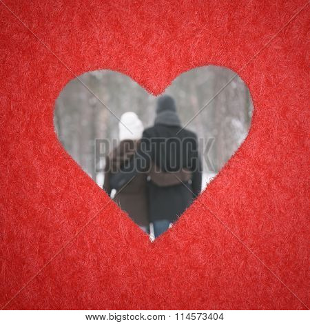 Hole in shape of heart. Plot is Valentines Day. A loving couple embracing in defocusing