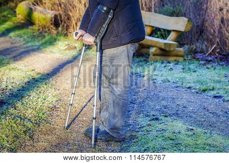 Disabled man on crutches at outdoor on the path