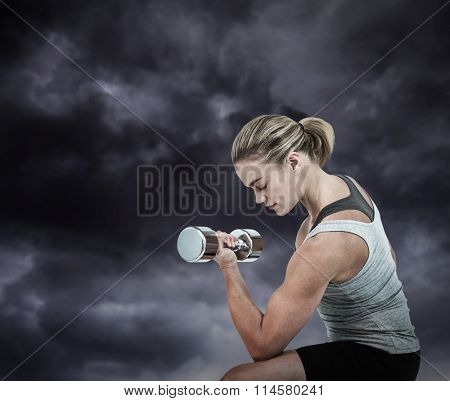 Muscular woman working out with dumbbells against gloomy sky Muscular woman working out with dumbbells on white background