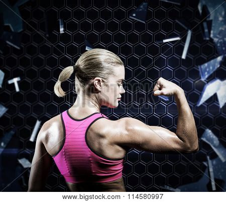 Muscular woman flexing her arm against glass shattering to show dark pattern