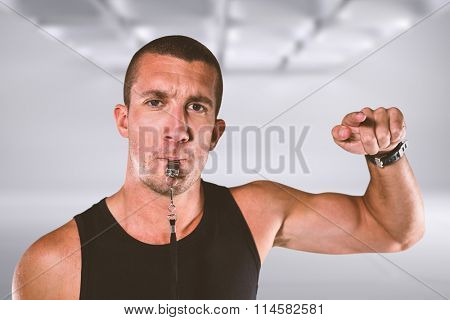 Portrait of attentive trainer blowing his whistle against white abstract room