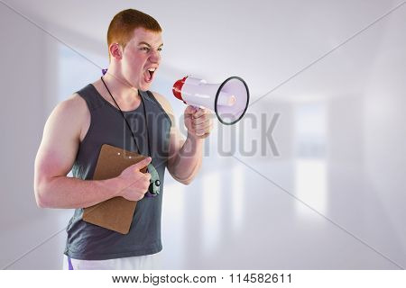 Angry personal trainer yelling through megaphone against bright white corridor with windows