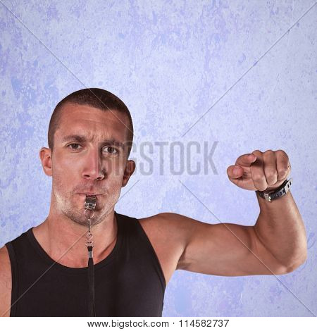 Portrait of attentive trainer blowing his whistle against purple background