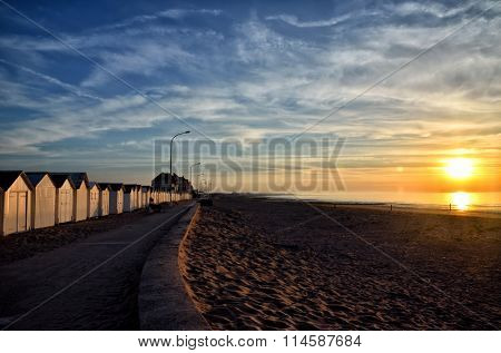Sunset at the beach in Normandy with bathing hut