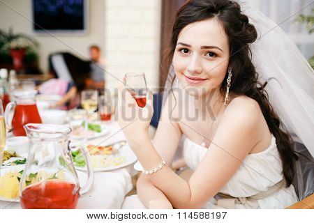 Attractive beautiful young bride in white dress sits at table with glass of red wine posing, kind ey