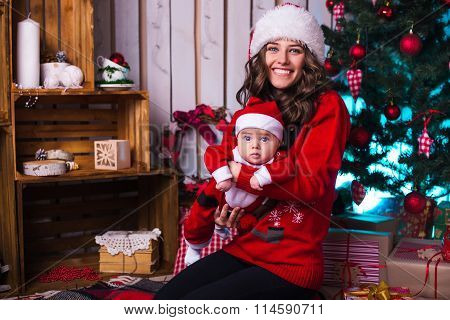 Portrait Of Happy Mother And Adorable Baby In Suit Of Santa's Little Helper