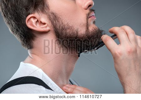 Healthy bearded young guy with sharp razor