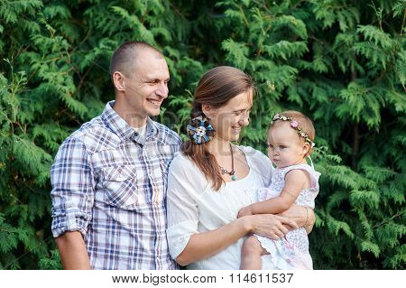 Happy Family With A Little Daughter On A Background Of Green Leaves
