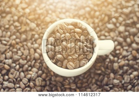 Coffee cup on a beans. Background from coffee beans. White cup. Full cup. Agriculture and seed.