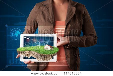 Young woman presenting a perfect ecology land with a house and windmills