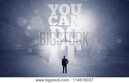 An unsure business person standing with his back in blue urban environment with big block letters saying you can do it concept