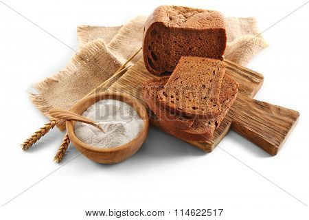 Sliced bread with ears and flour on napkin isolated on white