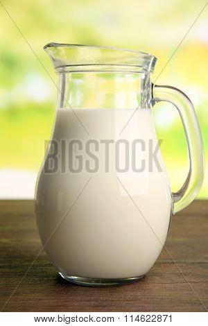 Jar of milk on blurred natural background
