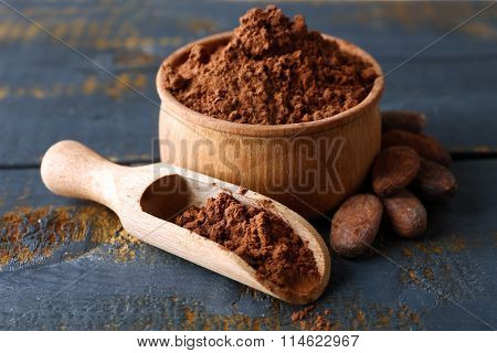 Bowl with aromatic cocoa powder on scratched wooden background, close up