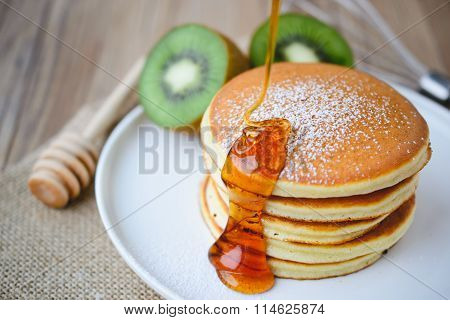 Pouring Syrup On Stack Of Pancake On White Plate And Sackcloth With Kiwi Slices On Wood Background