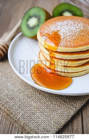 Pour Syrup On Stack Of Pancake On White Plate And Sackcloth With Kiwi Slices On Wood Background