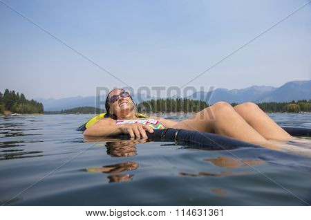 Woman relaxing in the summer sun floating in the water on the lake