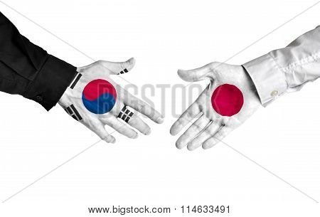 South Korea and Japan leaders shaking hands on a deal agreement