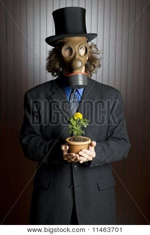 Man wearing a gas mask holding a flower