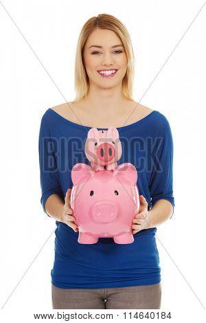 Happy woman with piggybanks.