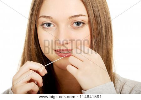 Teen woman with dental floss.