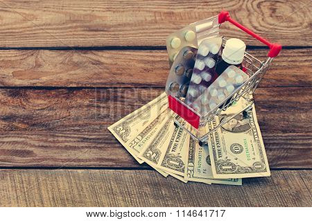 Shopping cart with pills, a syringe, candles, dollars on the old wood background. Toned image.