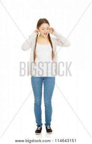 Teen woman covering ears with fingers.