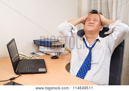 Frustrated And Stressful Asian Business Manager Behind Desk In Office