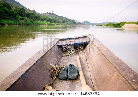 Wooden longtail boat heads out into the Mekong River
