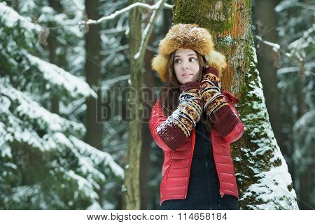 Winter outdoor portrait of student long-haired girl wearing warm down sweater and red fur trooper ha