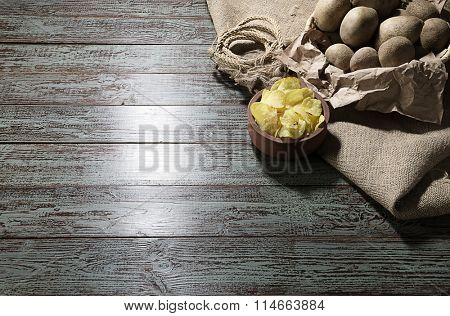 Raw potatoes and potato chips over brown wooden background.